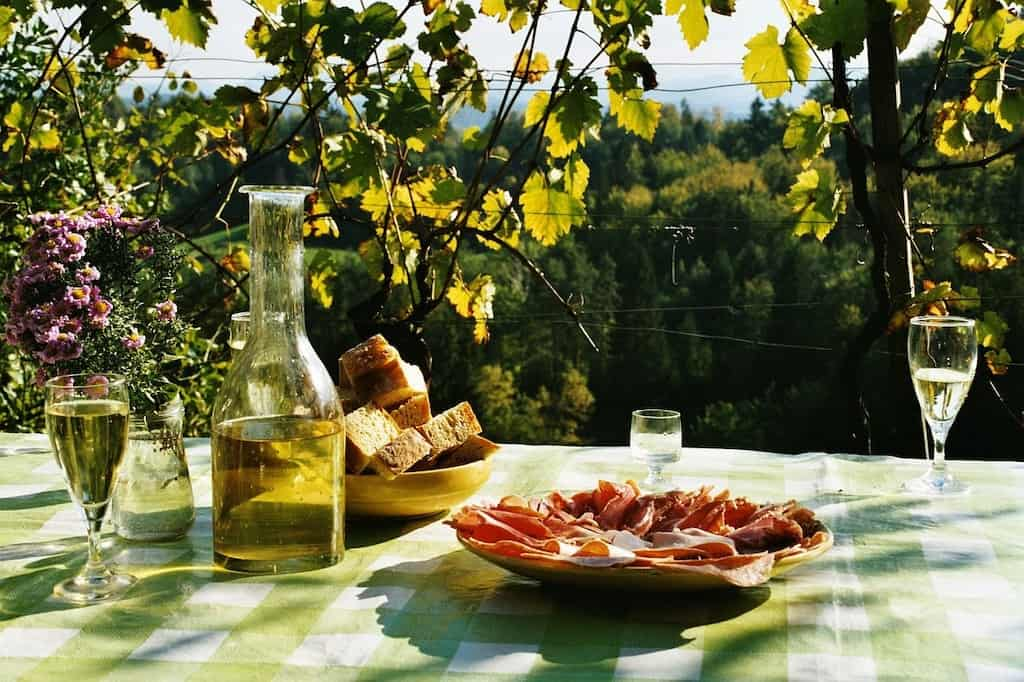 A outdoor table set up for a picnic with sliced meats, bread, and wine.