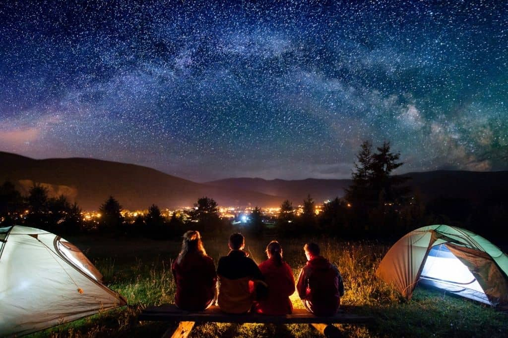 A group of friends sits around a campfire on a starry night.