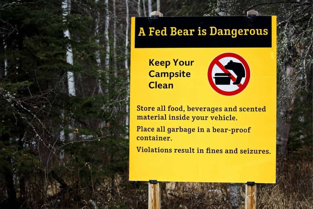 A campground sign warning campers about attracting bears to their campsites by leaving food out.
