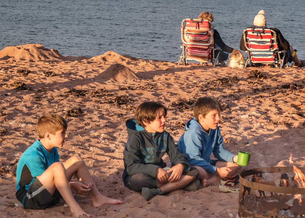 Three boys sit next to a campfire on the beach in Cape Breton Highlands National Park.