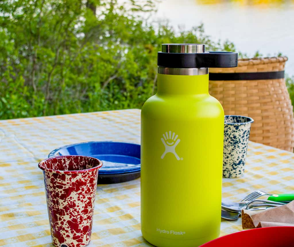 A Hydro Flask growler on a picnic table during a road trip picnic.