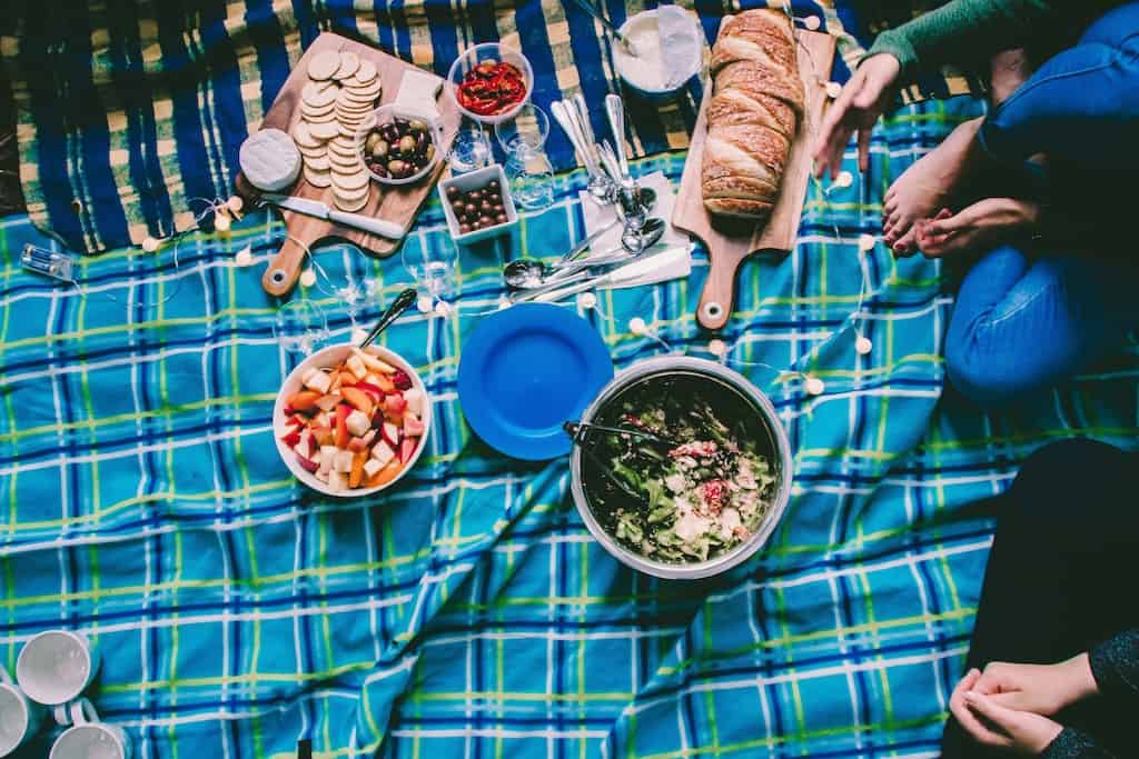 A spread of fabulous picnic food on a blue plaid blanket.