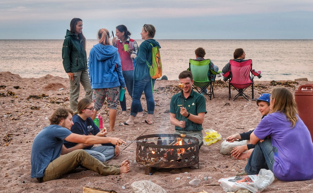 Several campers sit around a campfire on the beach at Broad Cove Campground in Cape Breton Highlands National Park.