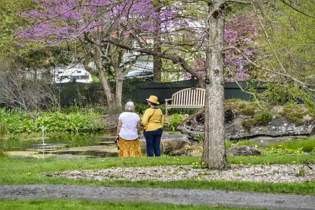 Two woman stand looking at the gardens and pond at the Berkshire Botanical Garden in Stockbridge, MA.