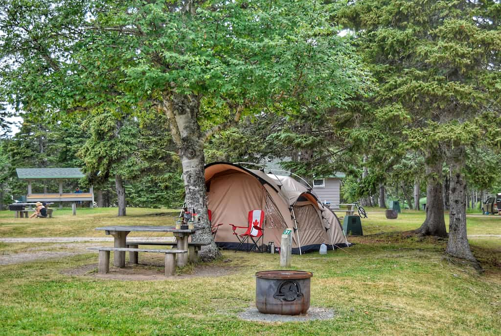 A tent is set up under some trees in Cape Breton Highlands National Park in Nova Scotia.