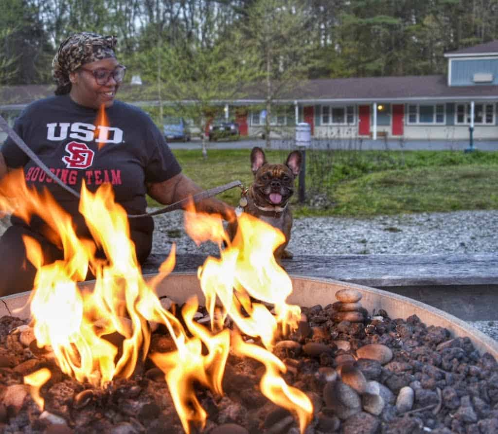 A woman sits with a French bulldog near a fire pit at the Briarcliff Motel in Great Barrington, MA.