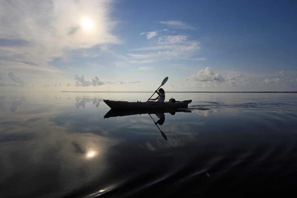 A woman paddles on the calm waters of Biscayne Bay in Florida.