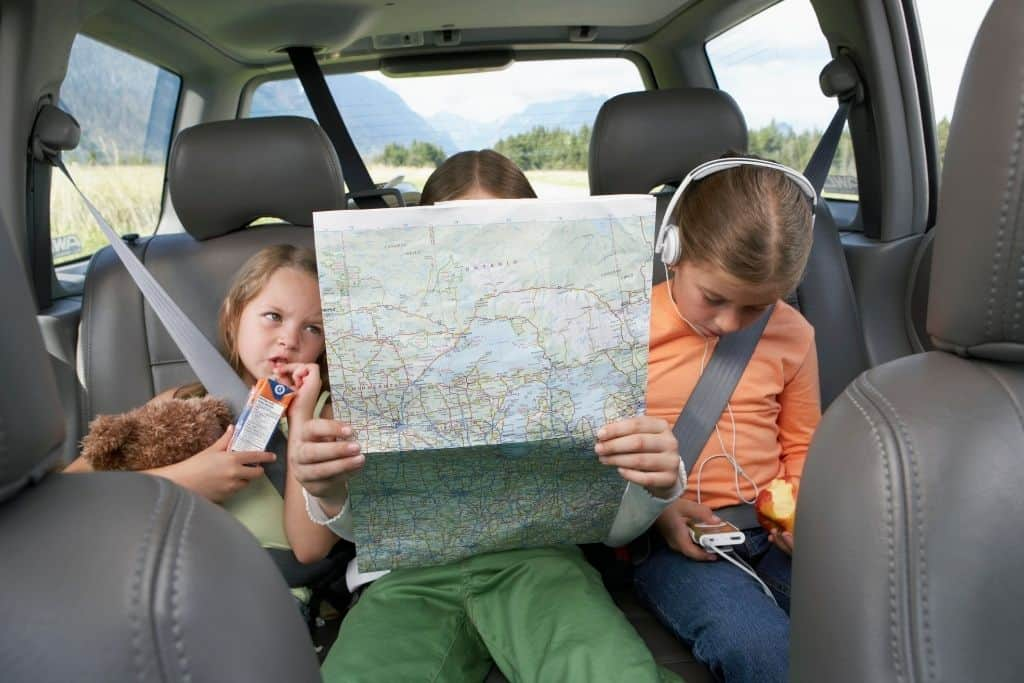 three kids in the backseat of a car looking at a map.