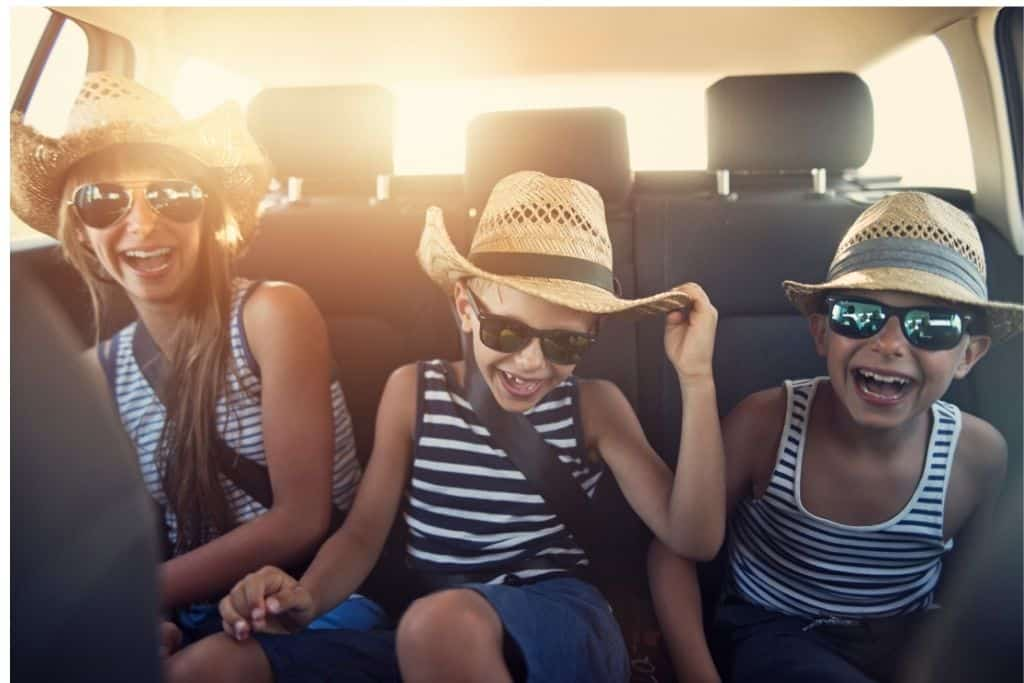 Three kids, all wearing straw hats and sunglasses, laugh in the back seat of a car during a family road trip.