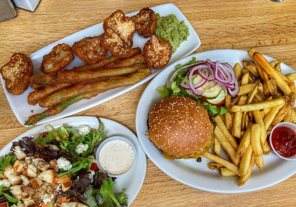 Our lunch at Grit in Caldwell, Idaho - a salad, burger with fries, and tempura asparagus and cauliflower.