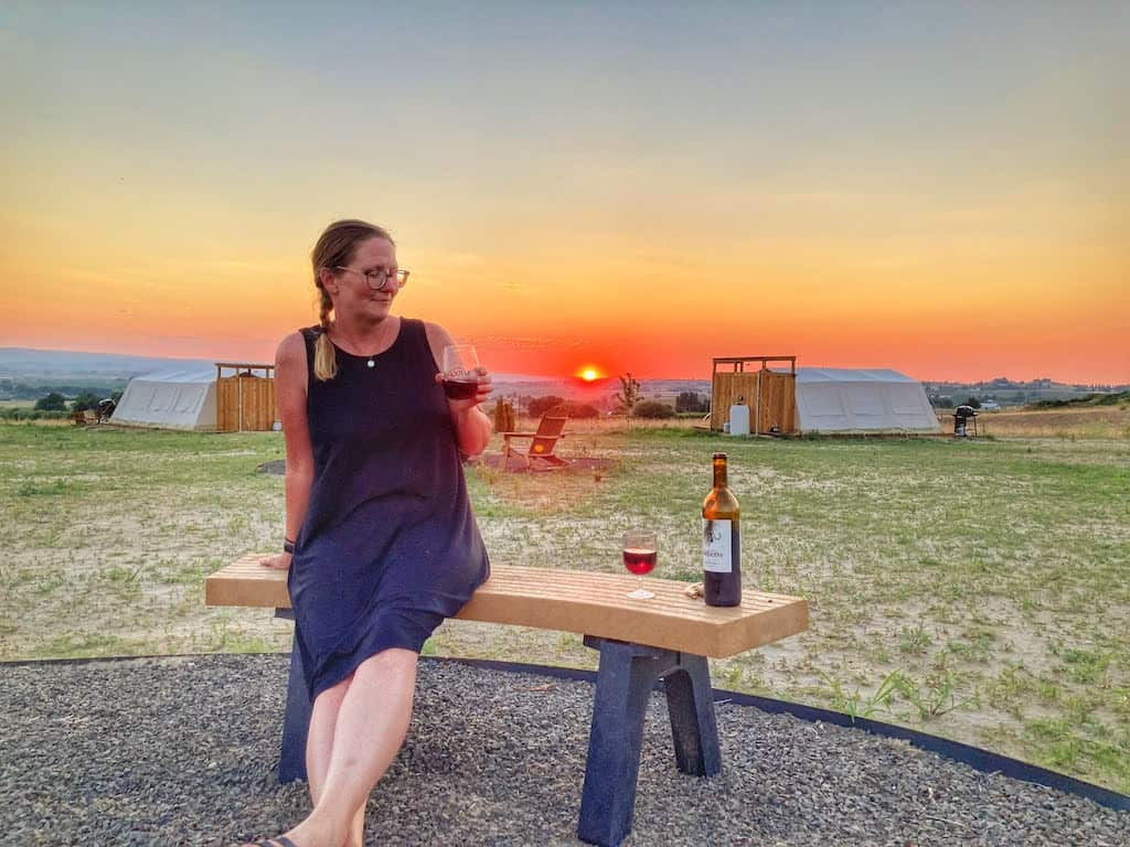 the sun sets behind me as I sip a glass of red wine from Sawtooth Winery in Caldwell, Idaho.