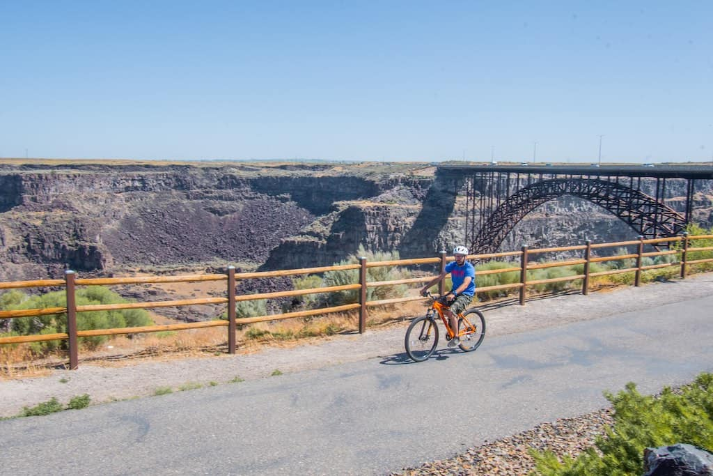 A bicyclist rides on the Canyon Rim Trail in front of the Perrine Bride in Twin Falls, Idaho. Photo credit: Visit Southern Idaho