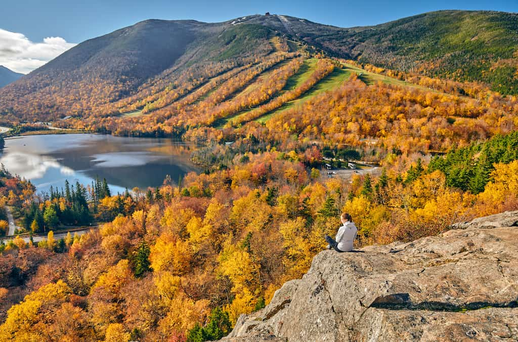 A woman sits on a rock outcropping at Artist's Bluff looking out over Echo Lake in Franconia Notch State Park in the fall.