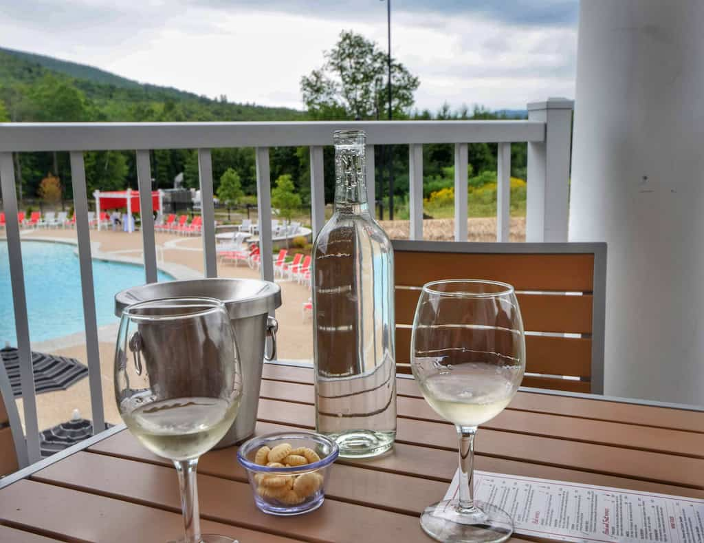 Two glasses of wine on a table on the balcony at RiverWalk Resort at Loon Mountain in Lincoln, New Hampshire.