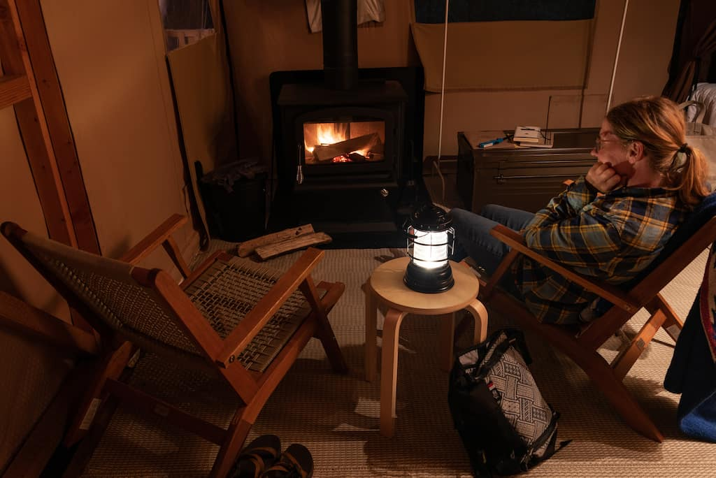 A woman sits near a woodstove while glamping in the Adirondacks at Huttopia.