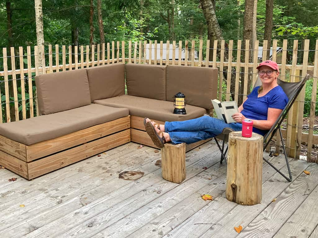 A woman sits on a balcony reading a book at Huttopia Adirondacks glamping in New York.