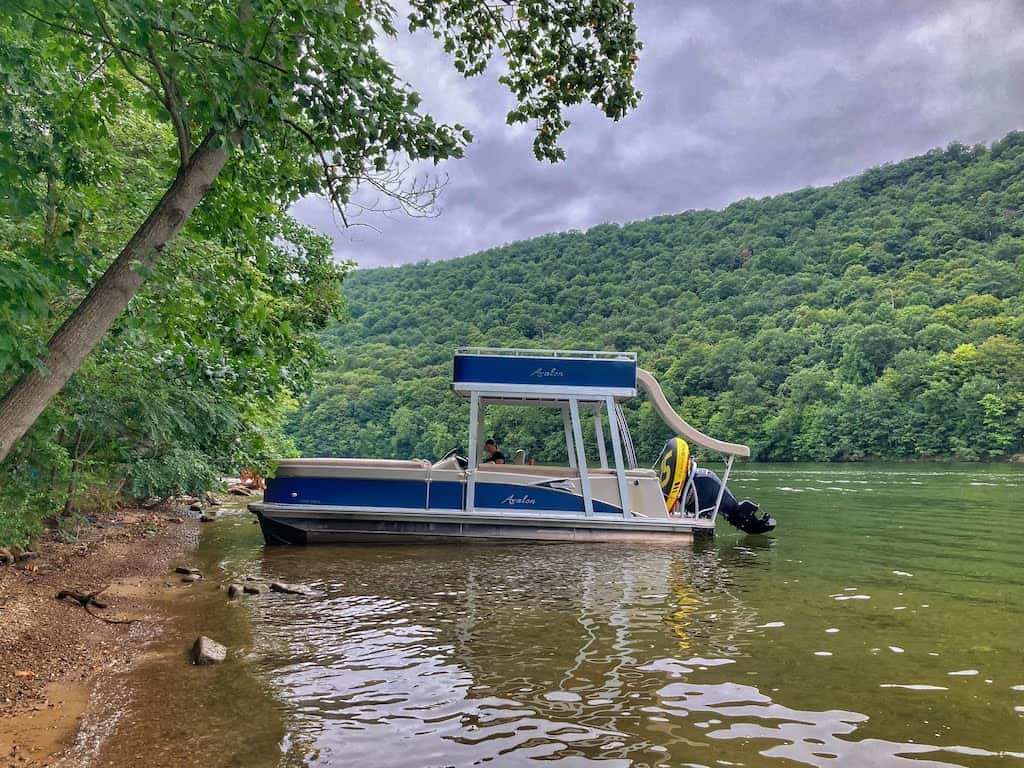 A pontoon boat with a slide on the back that is available for rent from Lake Raytsown Resort in Entriken, Pennsylvania.