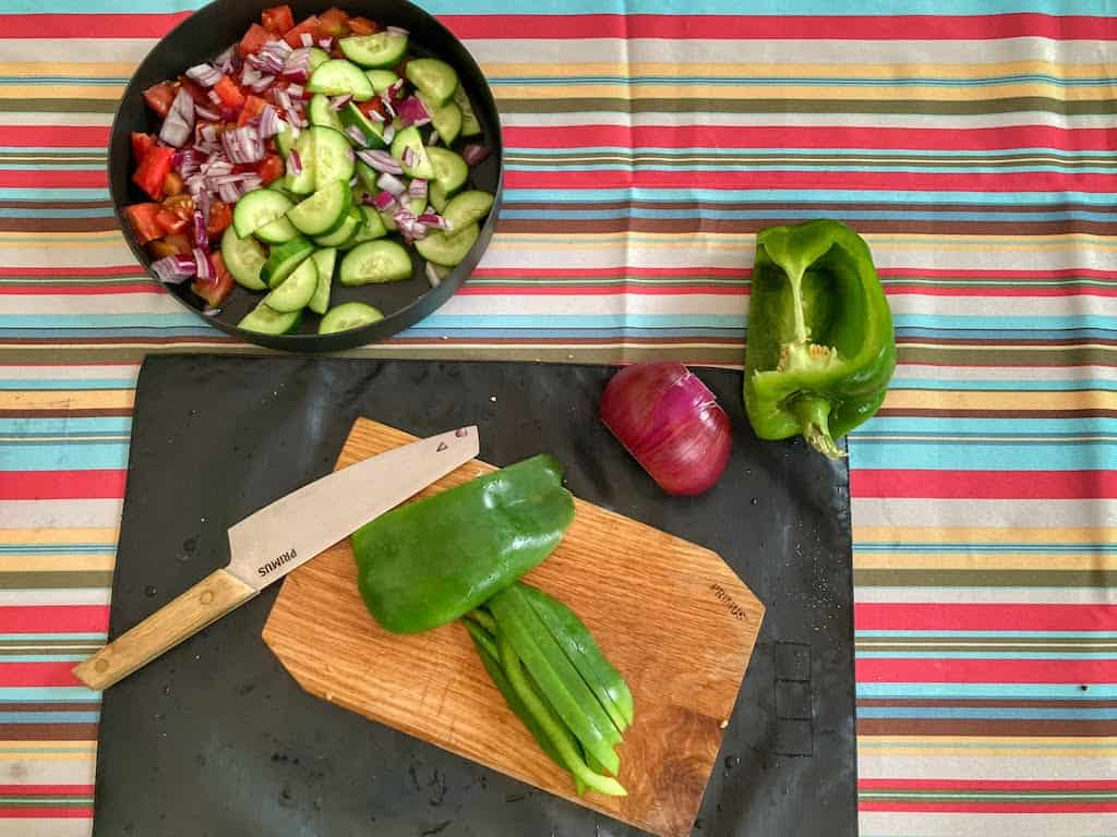 A cutting board and knife with a green pepper on it. Next to the board is a plate of panzanella camping salad and a red onion.