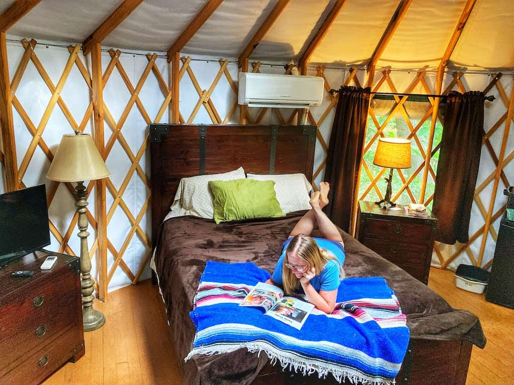 A woman lies on a bed in a yurt at Lake Raystown Resort in Pennsylvania.