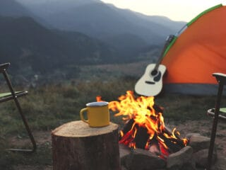 A yellow mug sits on a stump in front of a campfire. There is an orange tent and a guitar in the background.
